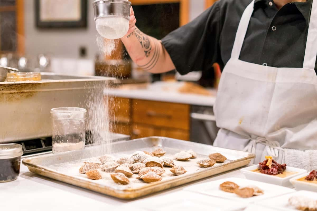 Baker adding powdered Sugar to sweets