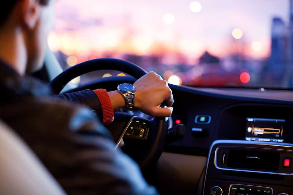 man driving a car wearing wrist watch