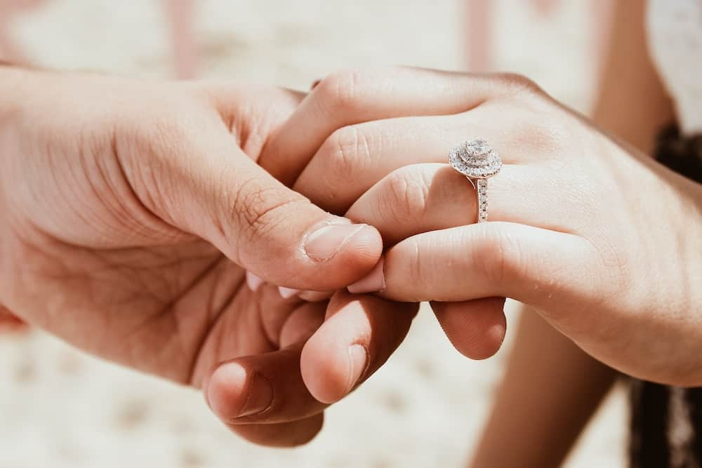 person holding another person hand with ring
