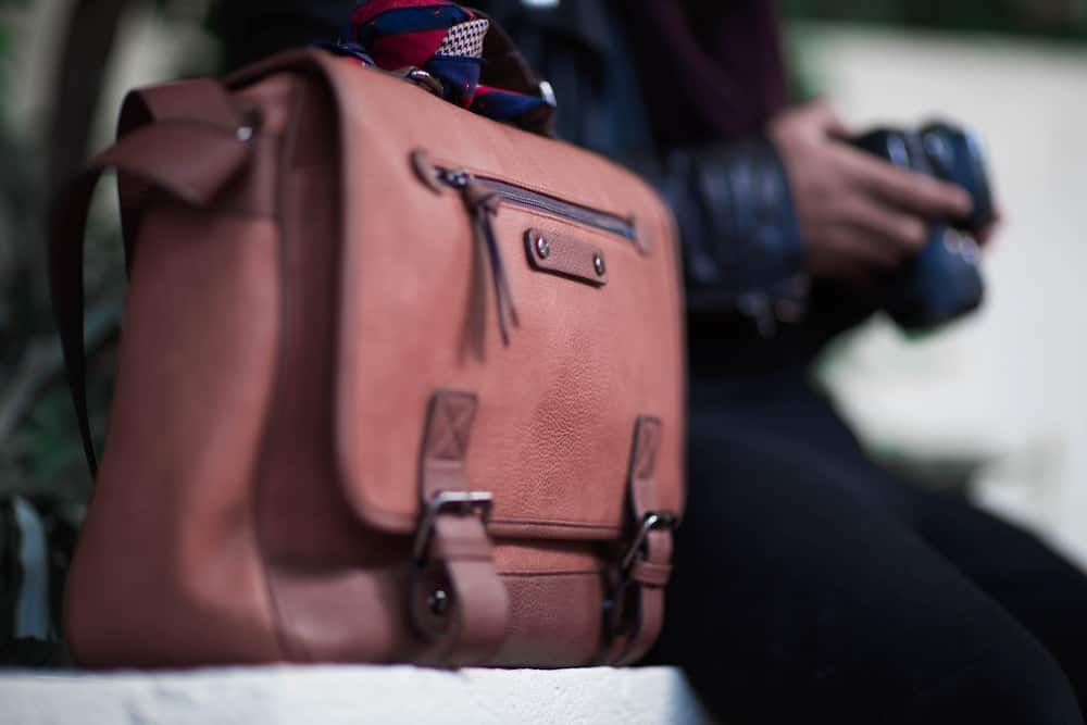 selective focus photogrtaphy of brown leather crossbody bag