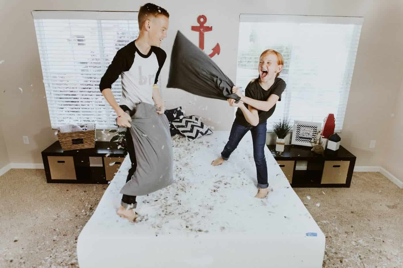 Two Kids Having a Pillow Fight on Their Bed