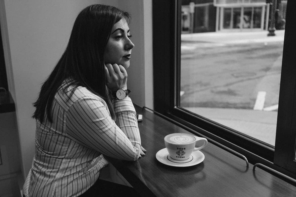 Lonely woman sitting inside a coffee shop