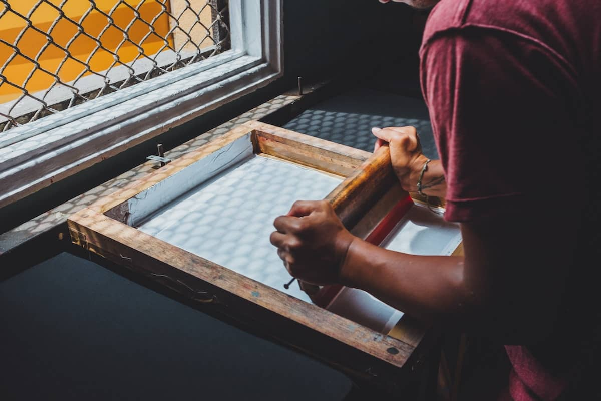 man holding printing screen near white window