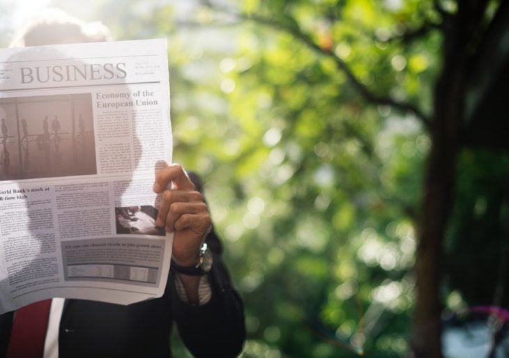 Man reading press release in the newspaper