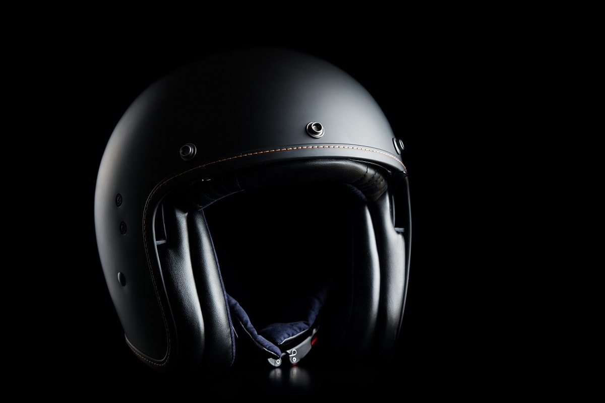 Open face motorcycle helmet on black background.
