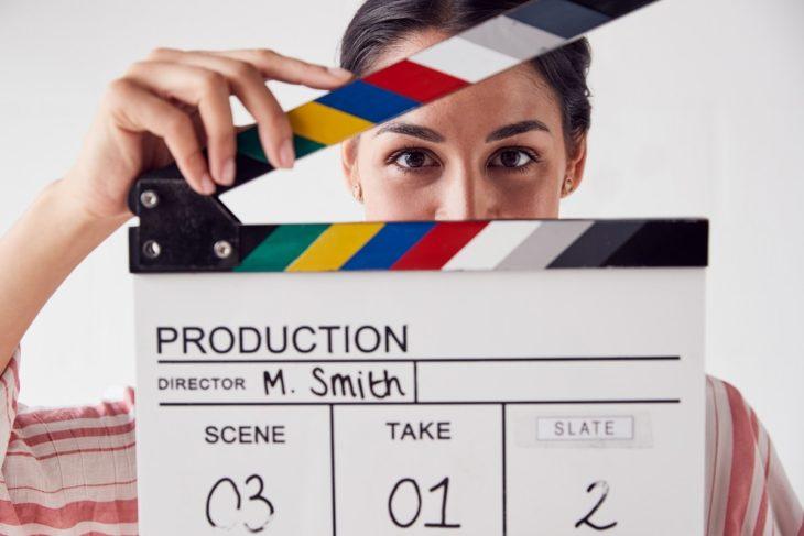 Portrait Of Female Videographer Holding Clapper Board On Video Film Production In White Studio
