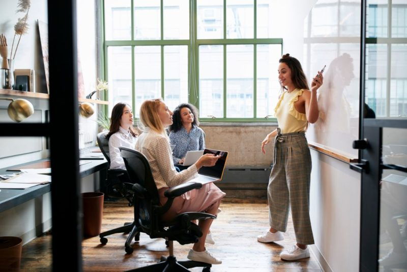 woman-pointing-at-whiteboard-in-a-meeting-with-PH34DPK-800x534