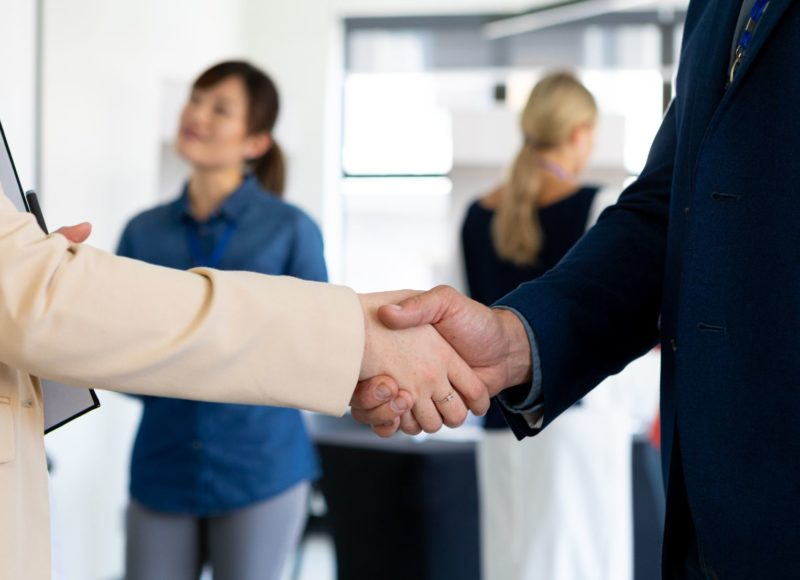 business-people-shaking-hands-in-a-office-5GVNN7K-800x580