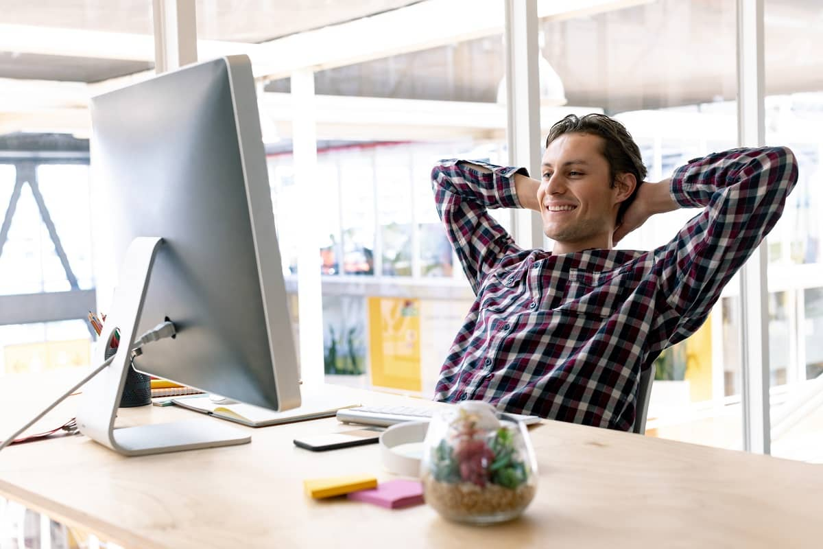 Happy Caucasian male graphic designer with hands behind head sitting on chair in a modern office