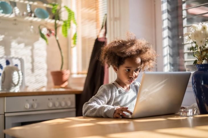 Kid using computer at home to learn programming