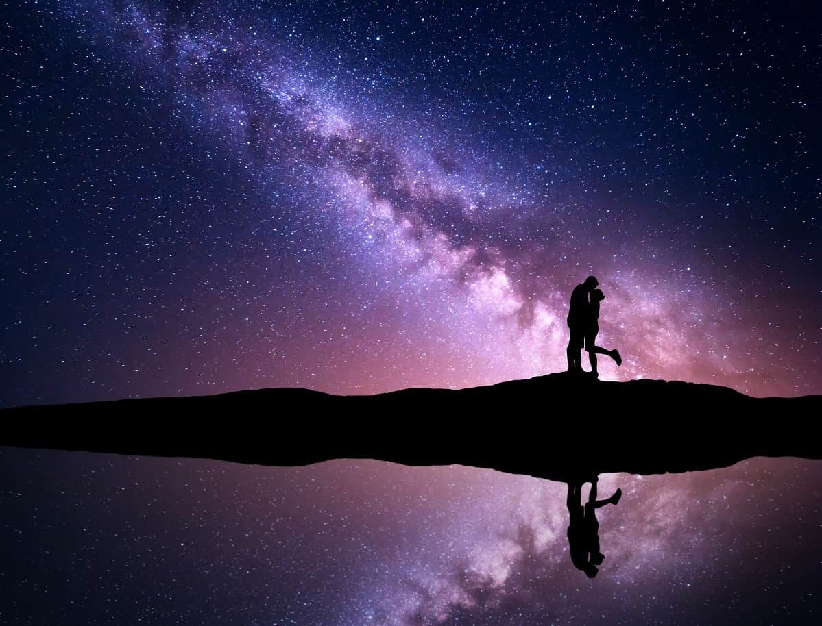 Milky Way. Silhouettes of hugging and kissing man and woman-min