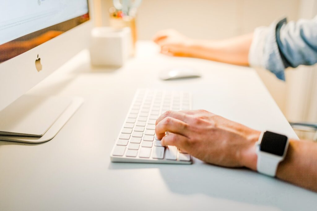 Man Using a White Keyboard on His Desk