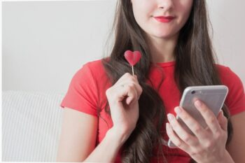 Girl with candy heart texting on smart phone
