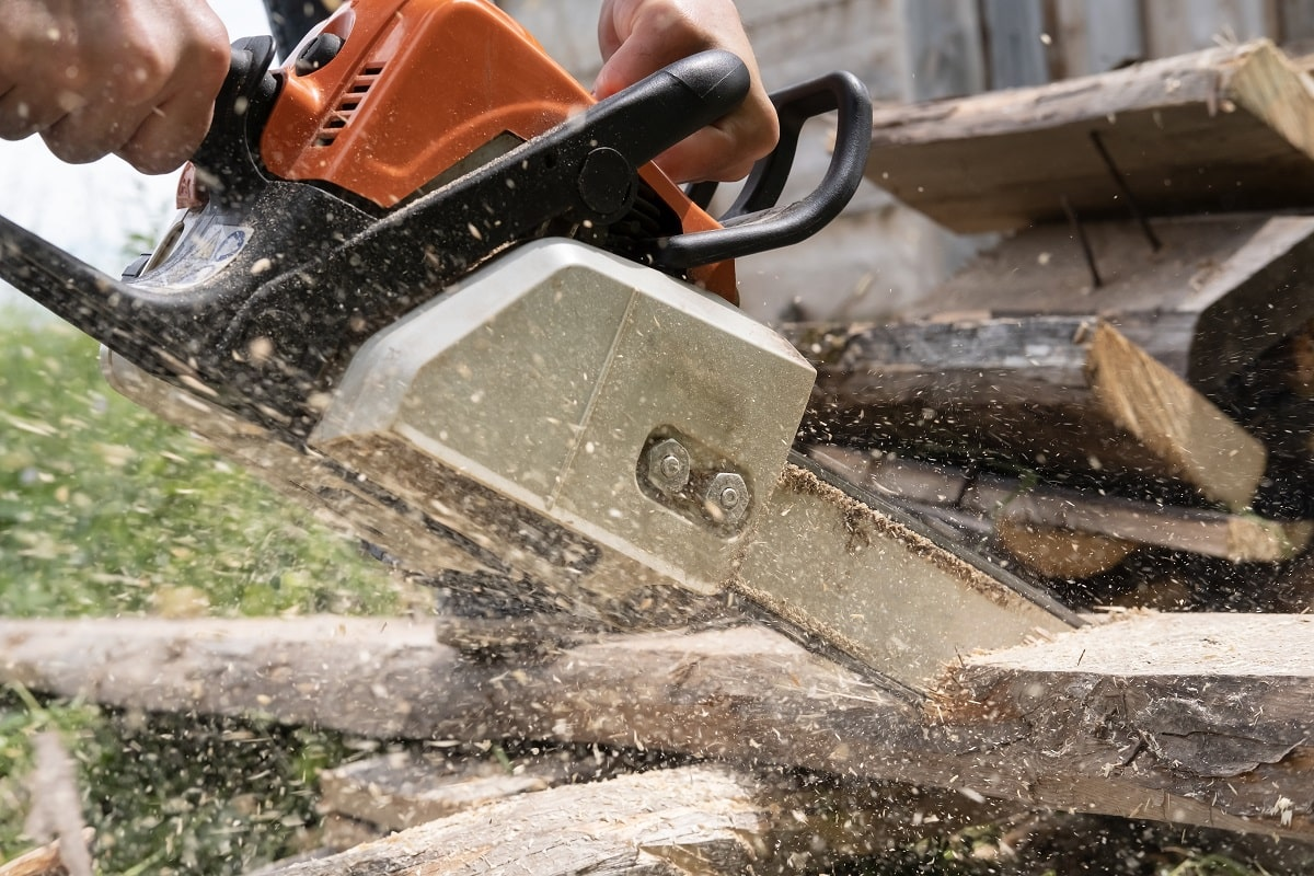 Male hands sawing old boards for firewood with a professional chainsaw