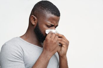 Guy having runny nose, touching his nose with napkin
