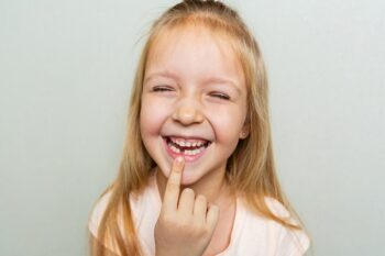 Happy little Caucasian girl with blonde hair showing missed milk tooth on gray background