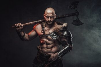 Holding axe on his shoulder savage nordic warrior in smokey background